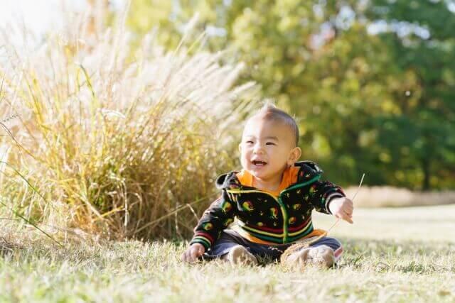 秋の公園でお座りしている赤ちゃんのイメージ画像